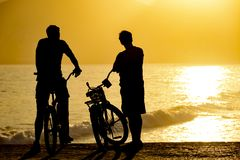 Two cyclists front the sea. Two cyclists during the late afternoon on the seafront watching the sunset royalty free stock photo