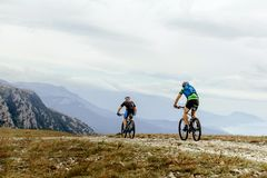 Two cyclists mountainbiker. Riding of background mountain peaks stock photography