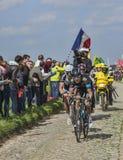 Two Cyclists on Paris Roubaix 2014. Carrefour de l'Arbre,France-April 13,2014: Two cyclists (Geraint Thomas- Sky, Bert De Backe- Giant Shimano) riding on the Stock Photos