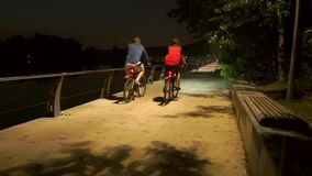 Two cyclists passing by on park embankment at late evening. Slow motion shot stock video footage