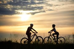 Two cyclists posing with bikes against amazing sky background. royalty free stock image