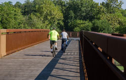 Two Cyclists without Protective Helmets. Roanoke County, VA – August 19th: A pair of cyclist enjoy a ride on the Roanoke River Greenway without protective Stock Images