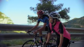 Two cyclists ride together in mountains stock video