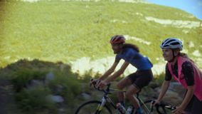 Two cyclists ride together in mountains. Softly focused hand held shot of two professional cyclists from sport team having fun during hard training, sprinting stock footage