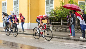 Two Cyclists Riding in the Rain. Gerardmer, France - 12.07.2014: The Belgian cyclist Jurgen Van den Broeck (Team Lotto Belisol) and the French cyclist Thibaut Royalty Free Stock Photos