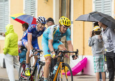 Two Cyclists Riding in the Rain. Gerardmer, France - 12.07.2014: The Danish cyclist Jakob Fuglsang (Team Astana) and the French cyclist Arnold Jeannesson(FDJ.fr Stock Photos