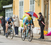Two Cyclists Riding in the Rain Stock Photos