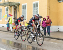 Two Cyclists Riding in the Rain - Tour de France 2014 Royalty Free Stock Photography