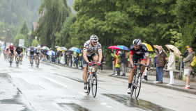 Two Cyclists Riding in the Rain - Tour de France 2014 Royalty Free Stock Image