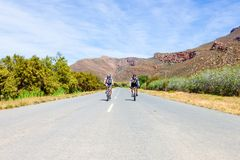 Two cyclists riding on a tar road in the Karoo Stock Photo