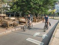 Two cyclists in Rio de Janeiro, Brazil. Rio de Janeiro, Brazil - Dec 19, 2017: Two cyclists on a cycling lane near Lagoa Rodrigo de Freitas at sunset in Rio de stock photography