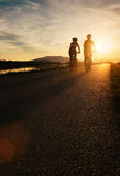 Two cyclists are on sunset road Stock Photos
