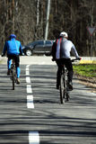 Two cyclists walk on wood road stock photography