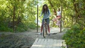 Two cyclists women descend from the hill. Two cyclists woman descend from the hill, telephoto shot stock footage
