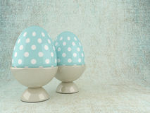 Two 3d Easter eggs in rack over rustic background Stock Photos