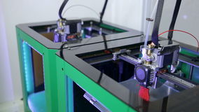 Two 3D printers creating objects. stock footage