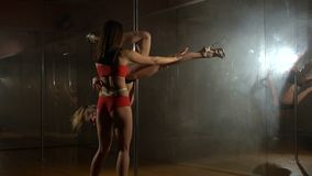 Two dancers girl pole dance training in the hall. Two sexy girls are engaged in dancing on the pole. The coach helps the girl to do a difficult exercise on the stock footage