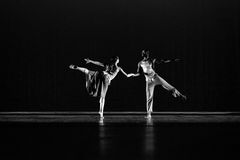 Two 2 dancers  pose against dark blue background on stage Royalty Free Stock Photo