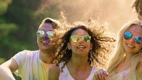 Two dancing couples covered in colored powder, happy friends enjoying party. Stock footage stock video