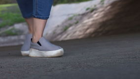 Two dancing female feet. Casual shoes on outdoor stock footage