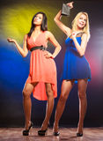 Two dancing women in dresses. Feminism and emacipation. Party, celabration, carnival. Two attractive dancing women in dresses on colorful background in studio royalty free stock photos