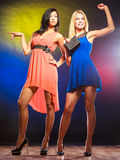 Two dancing women in dresses. Feminism and emacipation. Party, celabration, carnival. Two attractive dancing women in dresses on colorful background in studio stock photos