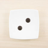 The two dark chocolate buttons and small white square disk Stock Photos