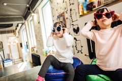 Two dark-haired sisters wearing leggings and light sweaters stock photo