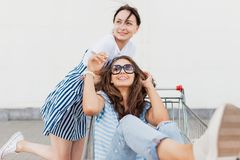 Two dark-haired slim pretty girls,wearing casual style,hug each other in a grocery cart near the mall. stock photos