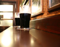 Two dark Irish stout beers. Two glasses of famous black Irish stout in pub on wooden bar Royalty Free Stock Images