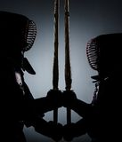 Two dark kendo fighters opposite each other Royalty Free Stock Image