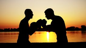 Two dark male figures, at sunrise, against the light, boxing, fighting in sparring, training in a pair of techniques of stock video