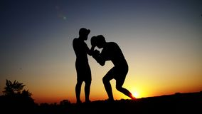 Two dark male figures, at sunrise, against the light, boxing, fighting in sparring, training in a pair of techniques of. Strikes. On sandy beach, in cargo port stock video footage