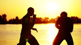 Two dark male figures, at sunrise, against the light, boxing, fighting in sparring, training in a pair of techniques of stock video footage