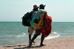 Two dark-skinned men, beach merchants walking along the shores stock images