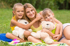 Two daughter kissing and hugging her mother lying on the grass on a picnic Royalty Free Stock Images