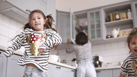 Two daughters are dancing on the kitchen, mother are cooking behind them