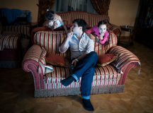 Two daughters disturbing father while watching TV at night Stock Photography