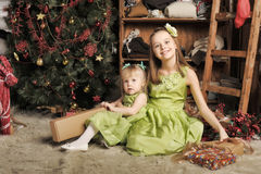 Two daughters in a green dress. At Christmas Royalty Free Stock Image