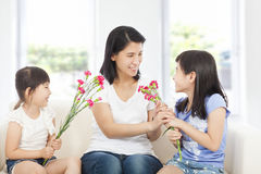 Two daughters handing mother carnations Royalty Free Stock Images