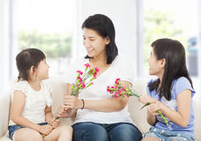 Two daughters handing mother carnations Stock Images