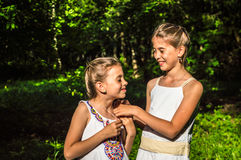 Two daughters hugging in the park Stock Photography