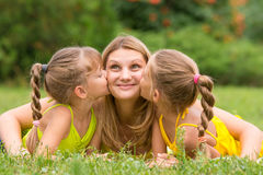 Two daughters kissing mother lying on grass on a picnic, Mother looked up fun. Two daughters kissing mother lying on the grass on a picnic, Mother looked up fun Stock Photos