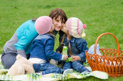 Two daughters kissing mother while on a picnic Royalty Free Stock Images
