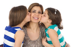 Two daughters kissing their mother Stock Images