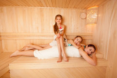 Two daughters lying on mothers back at sauna Royalty Free Stock Photos