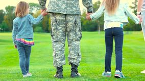 Two daughters of a soldier. Close up back view military father with kids standing together stock video footage