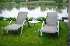 Two deck chairs on the bank of the river Royalty Free Stock Photos