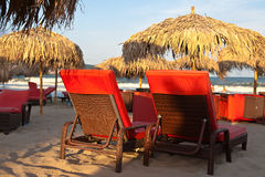 Two deck chairs on the beach. Red chairs and umbrellas on the beach Stock Images