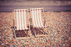 Two deck chairs on the beach. Two deck chairs on a pebble beach Royalty Free Stock Images